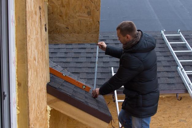 Couvreur mesurant des tuiles sur une nouvelle maison avec un ruban à mesurer alors qu'il se tient sur une échelle lors de l'installation du toit