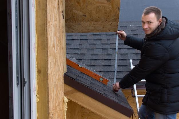 Couvreur sympathique installant de nouvelles tuiles de toiture prenant une mesure avec un ruban à mesurer alors qu'il se tient sur une échelle se tournant pour sourire à la caméra