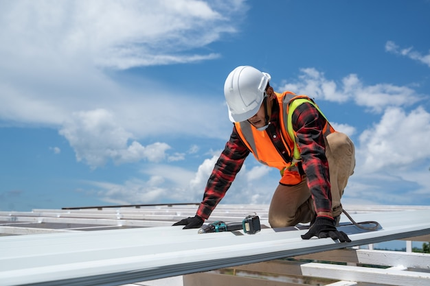 Couvreur travaillant dans des gants de protection, ouvrier de la construction portant un harnais de sécurité travaillant à haut niveau sur le chantier de construction installer un nouveau toit, toit en métal.
