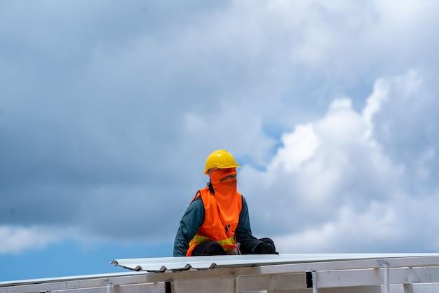 Couvreur travaillant à l'installation de toits en profilés métalliques, outils de toiture, perceuse électrique utilisée sur les nouveaux toits.