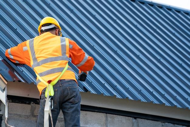 Couvreur travaillant sur la structure du toit du bâtiment sur le chantier de construction.