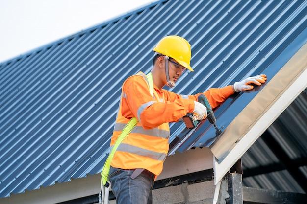 Couvreur travaillant sur la structure du toit du bâtiment sur le chantier, travailleur installant le toit métallique sur le toit de la nouvelle maison.