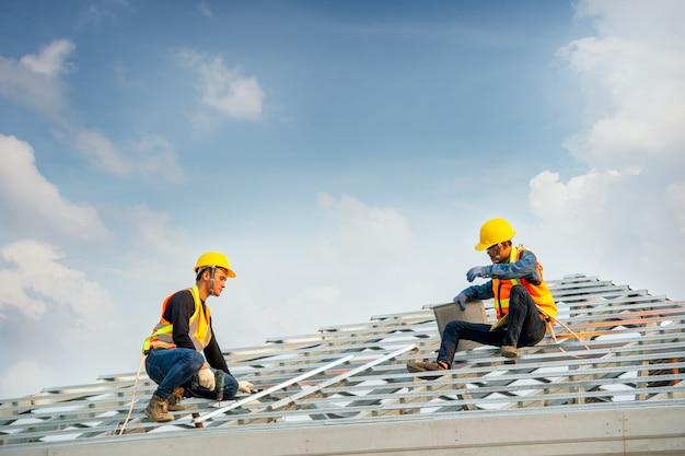 Couvreur utilisant un pistolet à clou pneumatique ou pneumatique et installant une tuile en béton sur le nouveau toit.