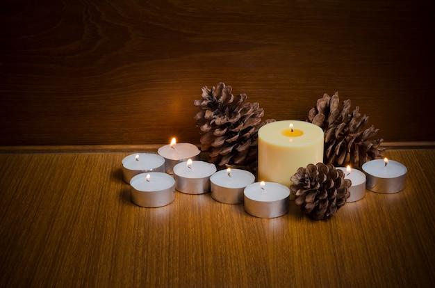 Couvrez les bougies jaunes et blanches avec des pommes de pin sur la table avec un espace pour la décoration de texte