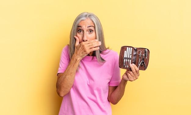 Couvrir la bouche avec les mains avec une expression choquée et surprise, garder un secret ou dire oups tenant un étui à outils pour les ongles