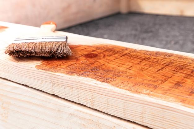 Couvrir la planche de bois avec l'agent protecteur avec une brosse pour meubles de petite entreprise