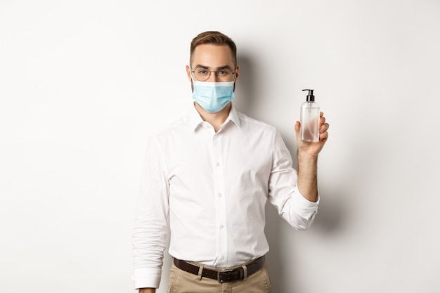 Covid-19, concept de distance sociale et de quarantaine. employeur en masque médical montrant un désinfectant pour les mains, demandant d'utiliser un antiseptique au travail, debout sur fond blanc.