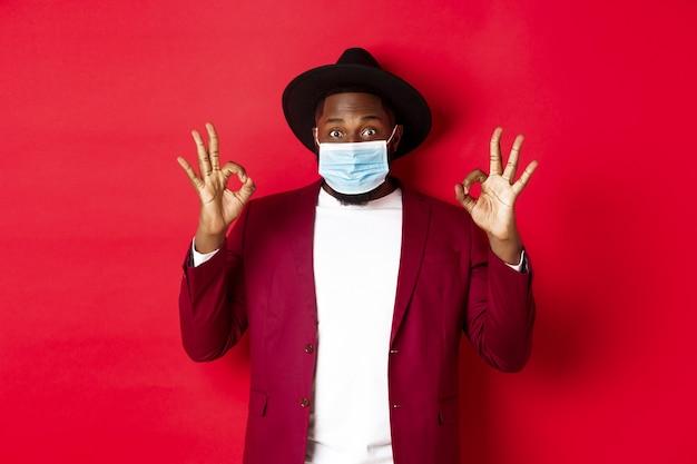 Covid-19 et concept de mode. homme afro-américain élégant en chapeau et blazer, portant un masque facial et montrant un signe d'accord, debout sur fond rouge