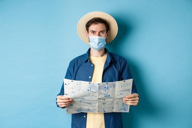 Covid-19, concept de pandémie et de voyage. heureux touriste en vacances d'été portant un masque médical et un chapeau de paille, tenant une feuille de route, debout sur fond bleu.