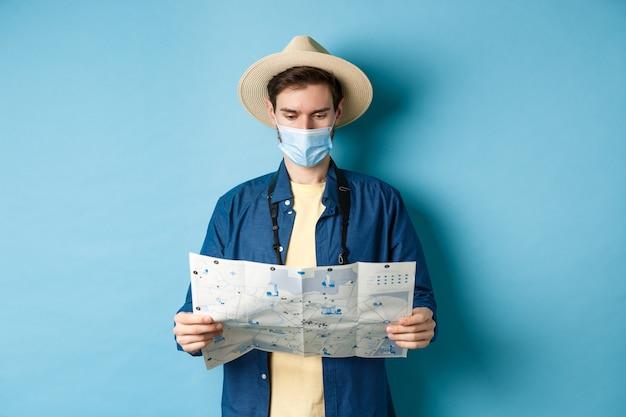 Covid-19, concept de pandémie et de voyage. jeune homme en masque médical, lecture de la carte touristique, à la recherche d'un itinéraire pour faire du tourisme, debout sur fond bleu.