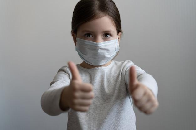 Covid-19 et concept de pollution de l'air. petite fille portant un masque pour protéger et geste de pouce vers le haut pour arrêter l'épidémie de virus corona. coronavirus et symptômes de virus épidémiques