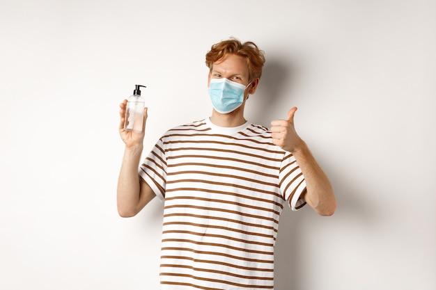 Covid-19, concept de santé et de style de vie. modèle masculin souriant aux cheveux roux, portant un masque facial, montrant un désinfectant pour les mains et le pouce vers le haut, recommande d'utiliser un fond blanc antiseptique.