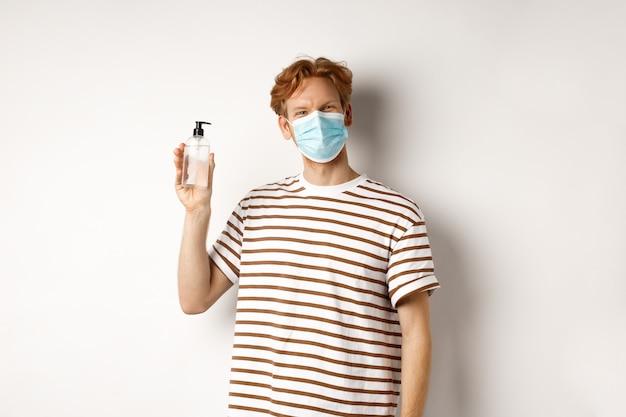 Covid-19, concept de santé et de style de vie. modèle masculin souriant aux cheveux roux, portant un masque facial, montrant un désinfectant pour les mains, recommande d'utiliser un fond blanc antiseptique.