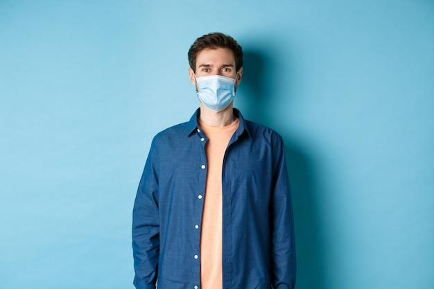 Covid-19 et concept de soins de santé. souriant jeune homme au masque médical à la recherche de santé et heureux, debout sur fond bleu.