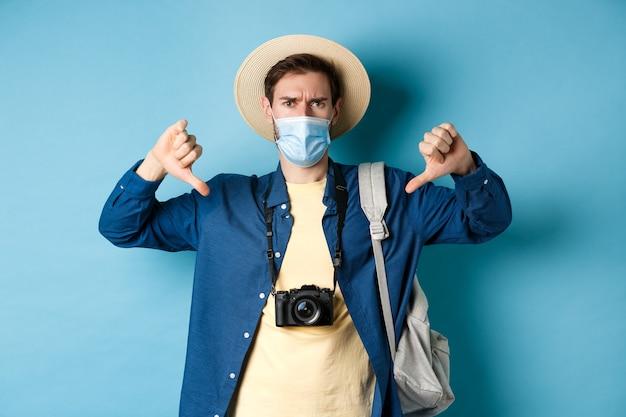 Covid-19 et concept de vacances d'été. touriste déçu en masque médical fronçant les sourcils, montrant les pouces vers le bas, commentaires négatifs sur le voyage, debout sur fond bleu.