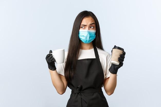 Covid-19, distanciation sociale, petite entreprise de café et concept de prévention des virus. barista asiatique pensant dans quelle tasse faire du café régulier ou à emporter pendant le coronavirus