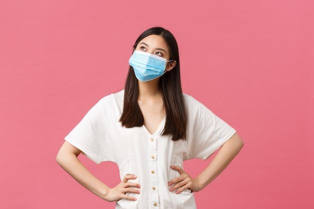 Covid-19, distanciation sociale, virus et concept de mode de vie. jolie fille asiatique rêveuse en robe blanche et masque médical contre le coronavirus, regardant l'imagerie dans le coin supérieur gauche, souriante heureuse