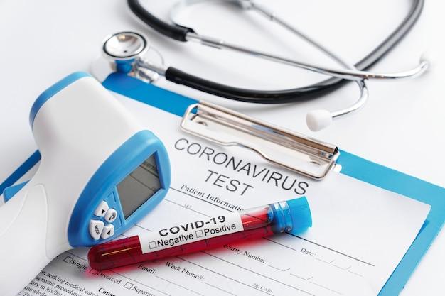 Covid-19 échantillons de sang, stéthoscope et thermomètre infrarouge numérique