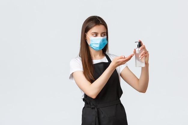 Covid-19, employés de café, cafés et concept de coronavirus. barista en masque médical et tablier noir utilisant un désinfectant pour les mains au travail pour prévenir le virus pendant la pandémie, en veillant à l'hygiène personnelle.