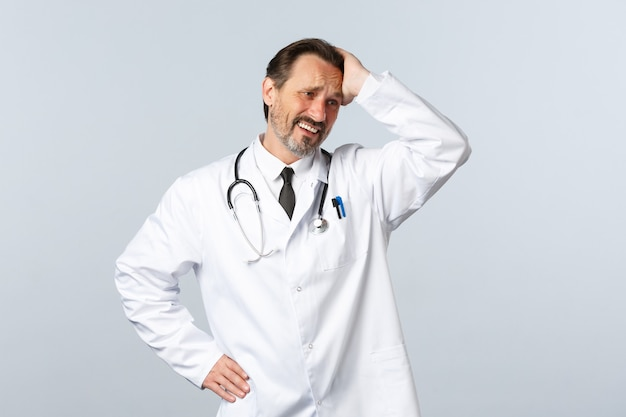 Covid-19, épidémie de coronavirus, travailleurs de la santé et concept de pandémie. médecin de sexe masculin désespéré troublé et inquiet en blouse blanche, touchant la tête et grimaçant, détournant les yeux en détresse