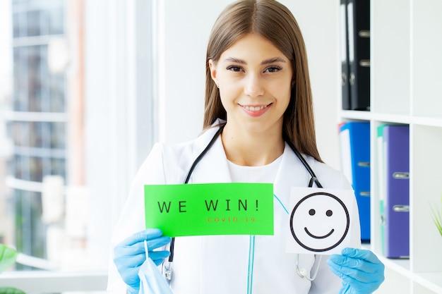 Covid-19, femme médecin tient un formulaire avec le texte que nous gagnons.