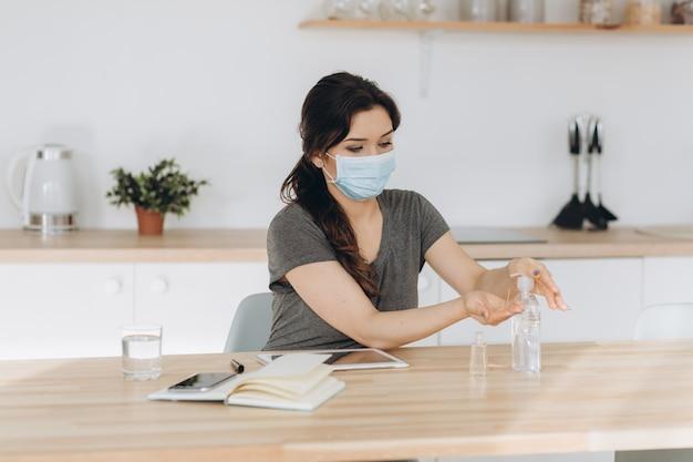 Covid-19 jeune femme utilisant un distributeur de gel désinfectant pour les mains contre le nouveau coronavirus (2019-ncov) à la maison. concept d'isolement à domicile, de quarantaine automatique, d'antiseptique, d'hygiène et de soins de santé.