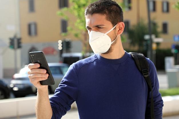 Covid-19 jeune homme portant un masque ffp2 utilisant un téléphone intelligent dans la rue de la ville