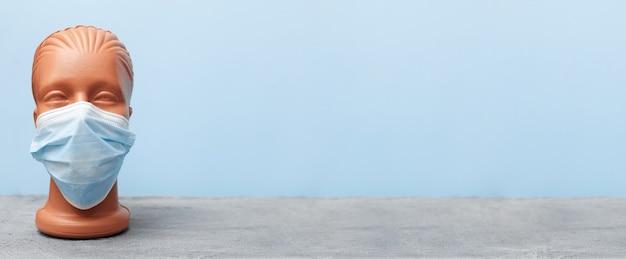 Covid 19, masque médical sur mannequin sur fond bleu, bannière, espace copie