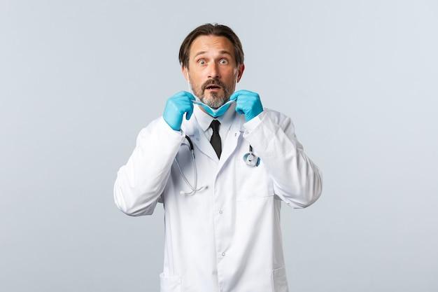 Covid-19, prévention du virus, travailleurs de la santé et concept de vaccination. un médecin préoccupé et inquiet en gants enlève un masque médical et regarde anxieux, découvrez des nouvelles choquantes