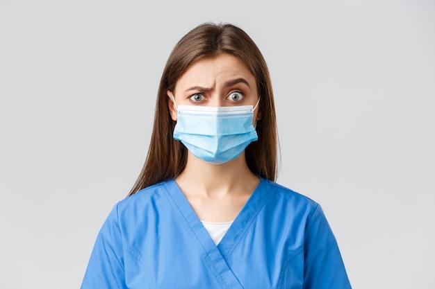 Covid-19, prévention des virus, santé, travailleurs de la santé et concept de quarantaine. jolie femme médecin ou infirmière en clinique, portant des gommages bleus et un masque médical sceptique ou méfiant