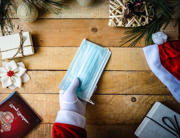 Covid christmas shot of santa mains dans des gants blancs tenant un masque sanitaire sur les décorations de noël
