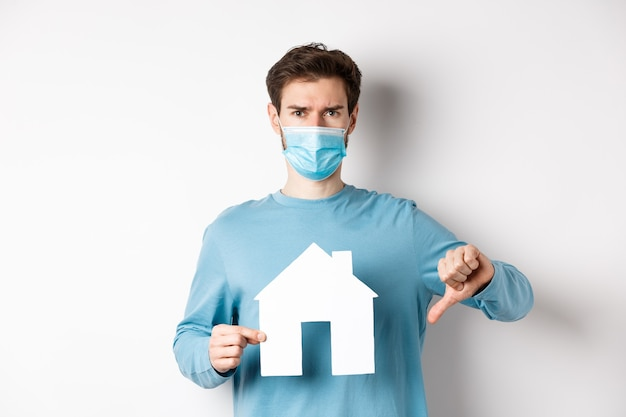Covid et concept immobilier. jeune homme déçu en masque médical montrant la découpe de la maison en papier et le pouce vers le bas, n'aime pas l'agence de courtage, debout mécontent sur fond blanc