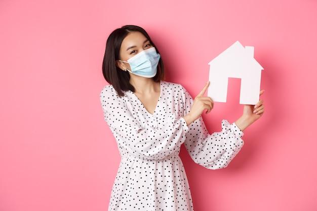 Covid immobilier et concept de mode de vie jolie femme asiatique en masque facial vendant des maisons montrant le modèle o ...