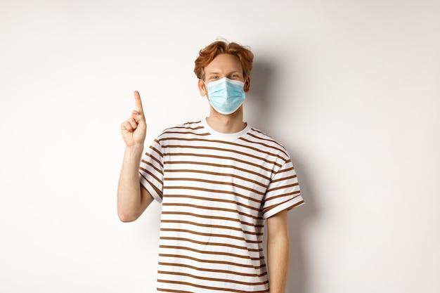 Covid, virus et concept de distanciation sociale. jeune étudiant aux cheveux roux, utilisant un masque facial du coronavirus, pointant le doigt vers le haut et souriant, fond blanc.
