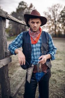 Cowboy brutal avec cigare dans le corral de chevaux