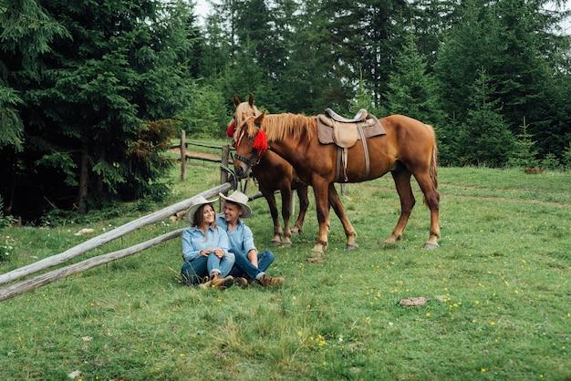 Cowboy et cowgirl dans les montagnes avec leurs chevaux