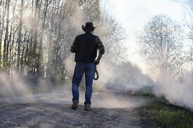 Un cowboy dans un chapeau et un gilet se tient dans une épaisse fumée sur la route