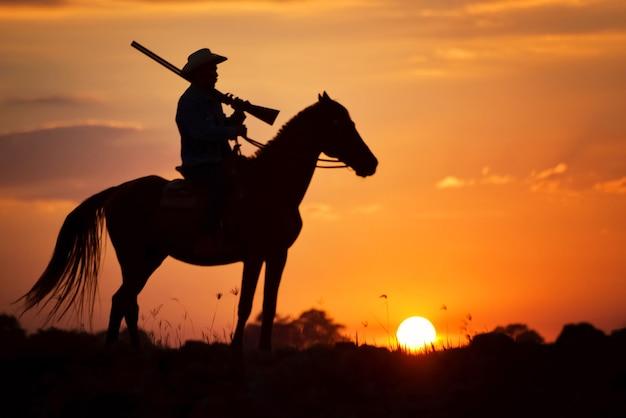 Cowboy silhouette à cheval sur sunset ang thong en thaïlande.