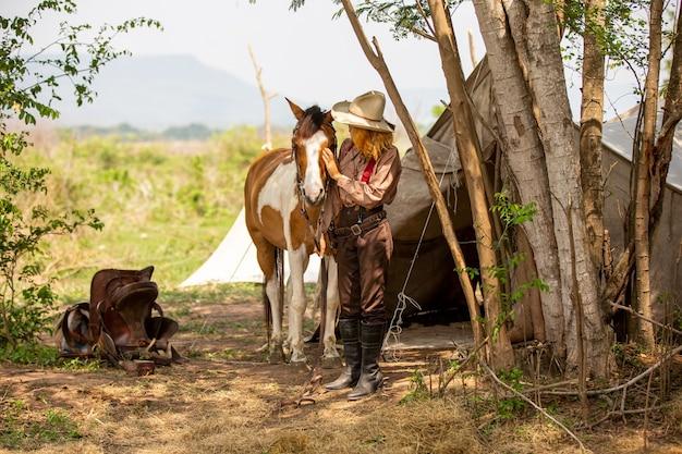 Cowgirl debout à cheval à la ferme en plein air
