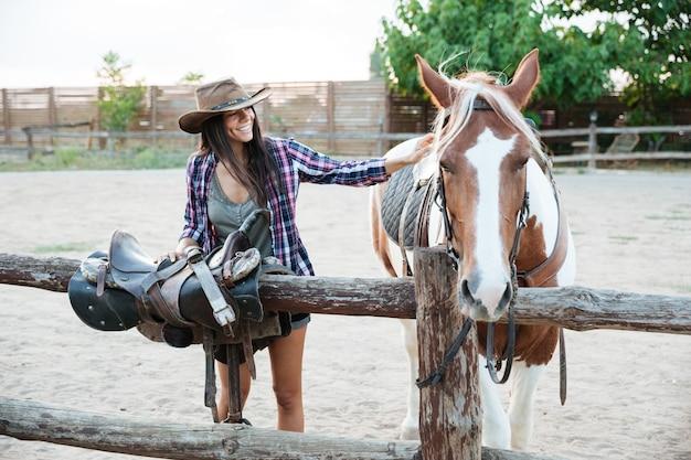 Cowgirl souriante de jeune femme au chapeau prenant soin du cheval et préparant la selle