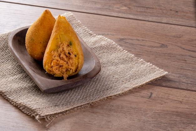 Coxinha frit dans un récipient en bois sur une table en bois.