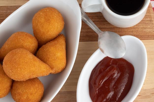 Coxinha de poulet servi avec du ketchup et du café noir.