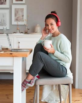 Cozy woman holding mug et assis sur une chaise
