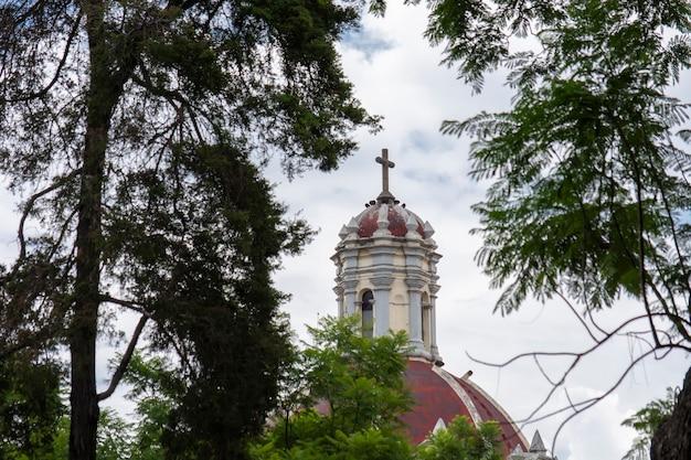 Cpula de iglesia con una cruz y las nubes y cielo azul al fondo