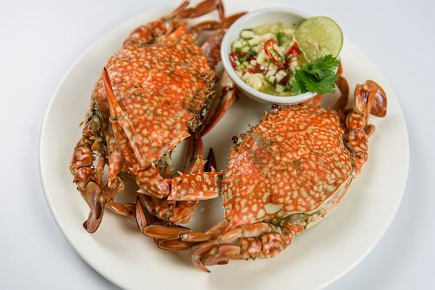 Crabe bleu cuit à la vapeur sur une assiette blanche avec une sauce aux fruits de mer épicée