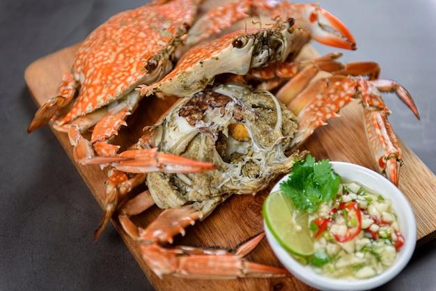 Crabe bleu cuit à la vapeur sur une assiette en bois avec sauce aux fruits de mer épicée, cuisine thaïlandaise