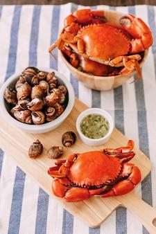 Crabe de boue géant cuit à la vapeur sur une planche à découper en bois servi avec une sauce aux fruits de mer épicée thaïlandaise et un canevas laevistrombus grillé dans une coquille.