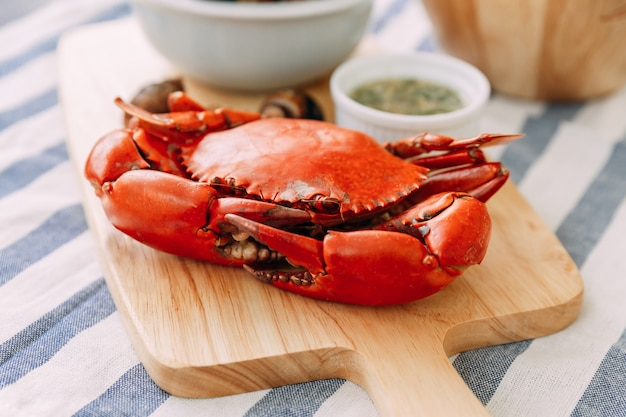 Crabe de boue géant cuit à la vapeur sur une planche à découper en bois, servi avec une sauce thaïlandaise épicée aux fruits de mer et un canarium grillé de laevistrombus en fond.