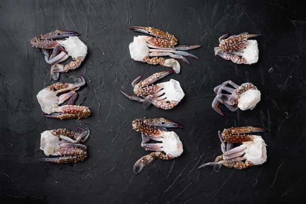 Crabe de cheval cru frais, crabe bleu, ensemble de crabe fleur, sur fond noir, vue de dessus à plat