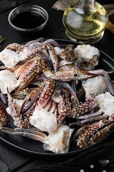 Crabe cru frais, crabe bleu, crabe fleur, ensemble sur fond de table en bois noir
